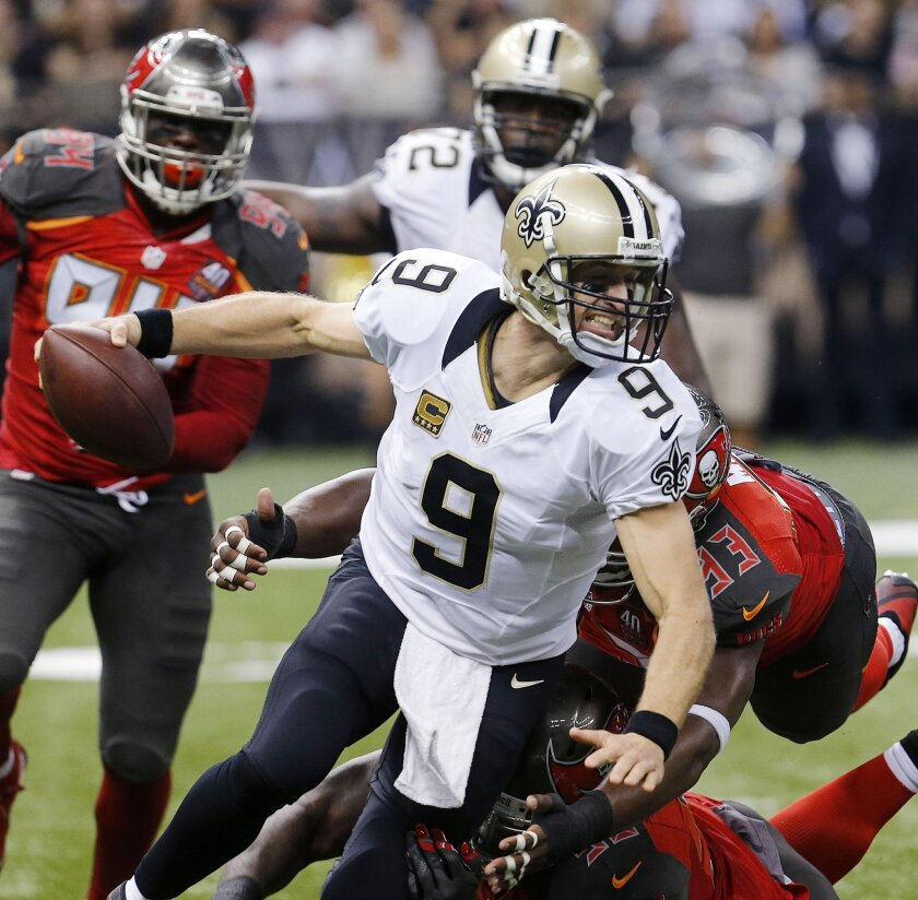 New Orleans Saints quarterback Drew Brees (9) is wrapped up by Tampa Bay Buccaneers defensive tackle Gerald McCoy (93) as he scrambles in the first half of an NFL football game against the Tampa Bay Buccaneers in New Orleans, Sunday, Sept. 20, 2015. The Buccaneers won 26-19. The Buccaneers won 26-19. (AP Photo/Bill Haber)