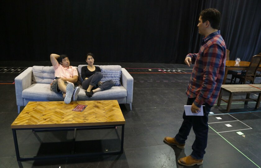 """Director Jaime Castaneda (right) talks with actors Raymond J. Lee and Jackie Chung during a rehearsal for """"Tiger Style!"""" at La Jolla Playhouse."""
