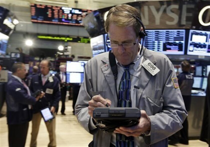 Trader Luke Scanlon, right, works on the floor of the New York Stock Exchange Monday, July 8, 2013. Stocks rose in early trading Monday ahead of the start of second-quarter corporate earnings reports. (AP Photo/Richard Drew)