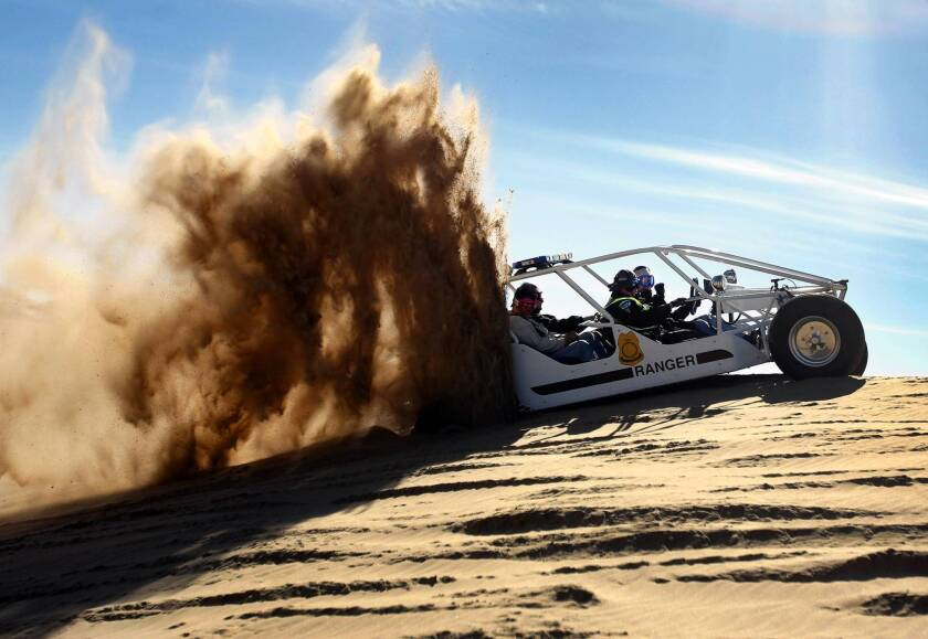Former Interior Secretary Ken Salazar tries to accelerate his sand rail while getting stuck on a sand hill during a tour of the Imperial Sand Dunes in 2011.