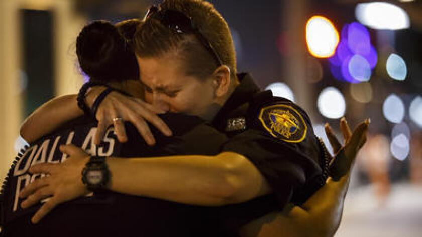 Police Officer Katherine Rhodes, right, embraces Officer Yuridia Morales at a memorial for the shooting victims.
