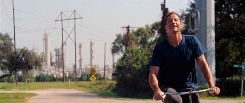 Simon Rex leans his head back and smiles as he rides a bike.