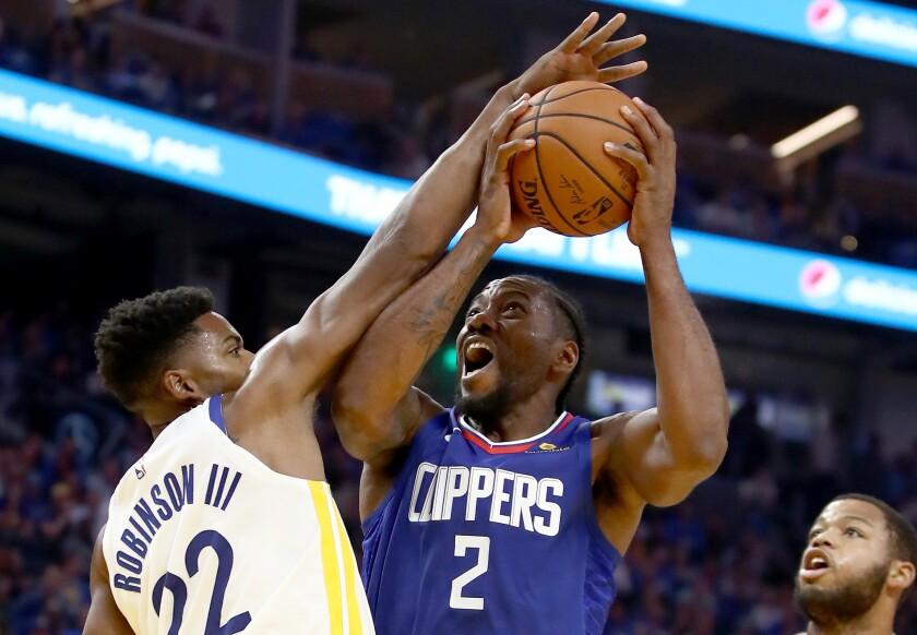Clippers star Kawhi Leonard, right, puts up a shot over Golden State forward Glenn Robinson III.