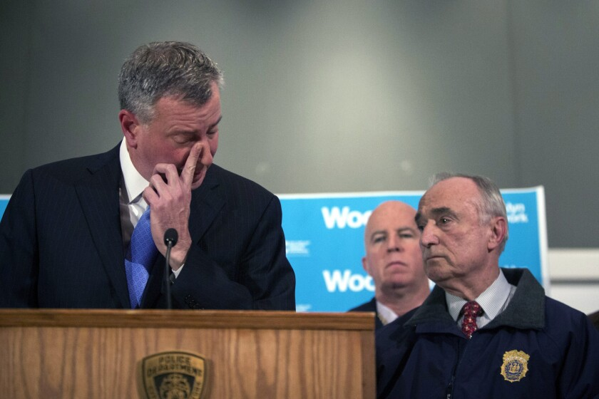 """An emotional New York Mayor Bill de Blasio speaks to the media about the officers' shootings, which he called """"particularly despicable."""""""
