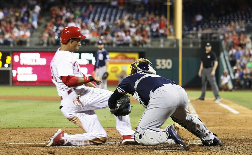 Philadelphia Phillies' Aaron Altherr left, is tagged out at home by San Diego Padres' Derek Norris after stealing second and continuing on to home during the fourth inning of a baseball game Saturday, Aug. 29, 2015, in Philadelphia. (AP Photo/Tom Mihalek)