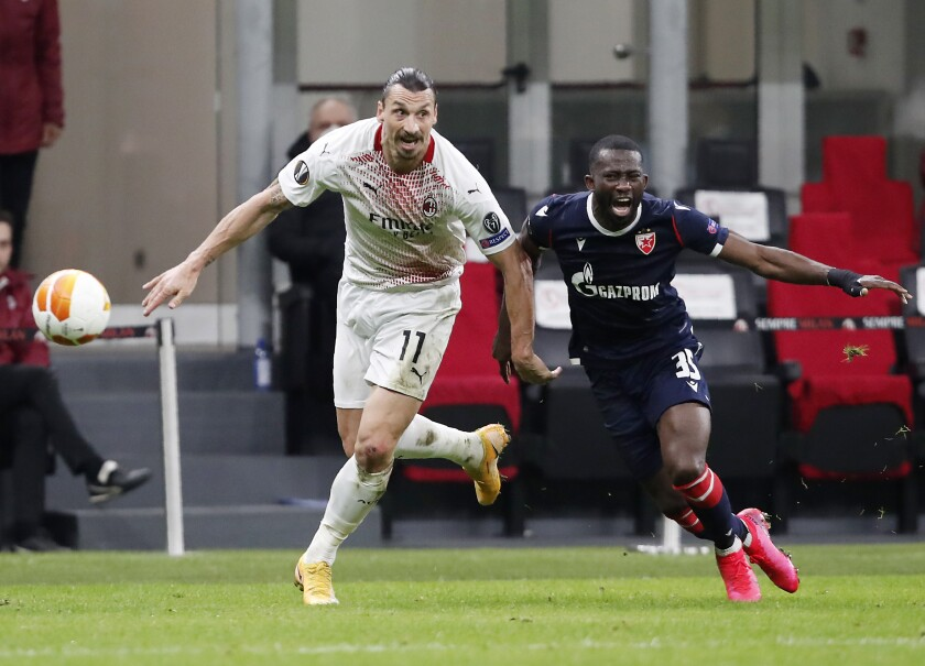 AC Milan's Zlatan Ibrahimovic, left, challenges for the ball with Red Star's Sekou Sanogo during the Europa League round of 32 second leg soccer match between AC Milan and Red Star Belgrade at the San Siro Stadium, in Milan, Italy, Thursday, Feb. 25, 2021. (AP Photo/Antonio Calanni)