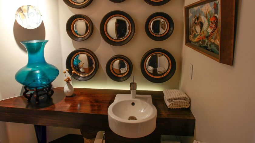 The remodeled powder room-bathroom at the Brion home includes a Macassar ebony wood counter.
