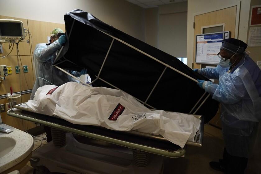 In this Jan. 9, 2021 file photo, transporters Miguel Lopez, right, Noe Meza prepare to move a body of a COVID-19 victim