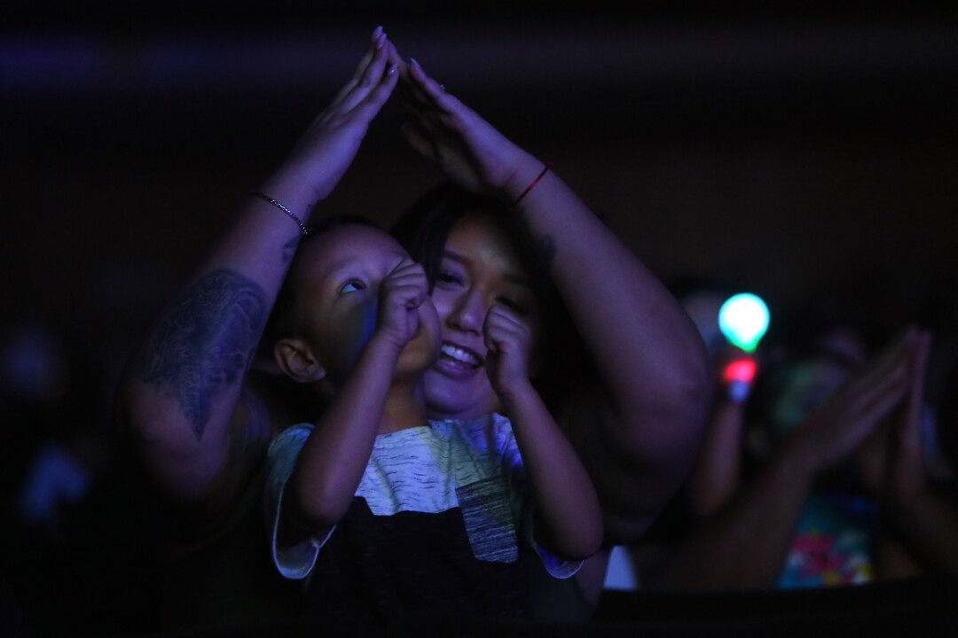 Three-year-old Julian Prum sings along with his mom, Jessica Maggart,