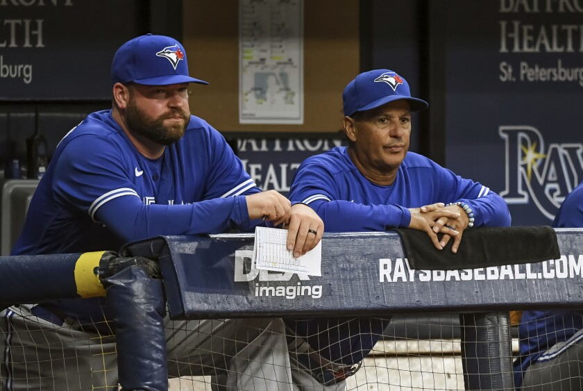 Toronto Blue Jays coach John Schneider, left, and manager Charlie Montoyo watch from the dugout during the eighth inning of a baseball game against the Tampa Bay Rays, Saturday, July 10, 2021, in St. Petersburg, Fla.(AP Photo/Steve Nesius)