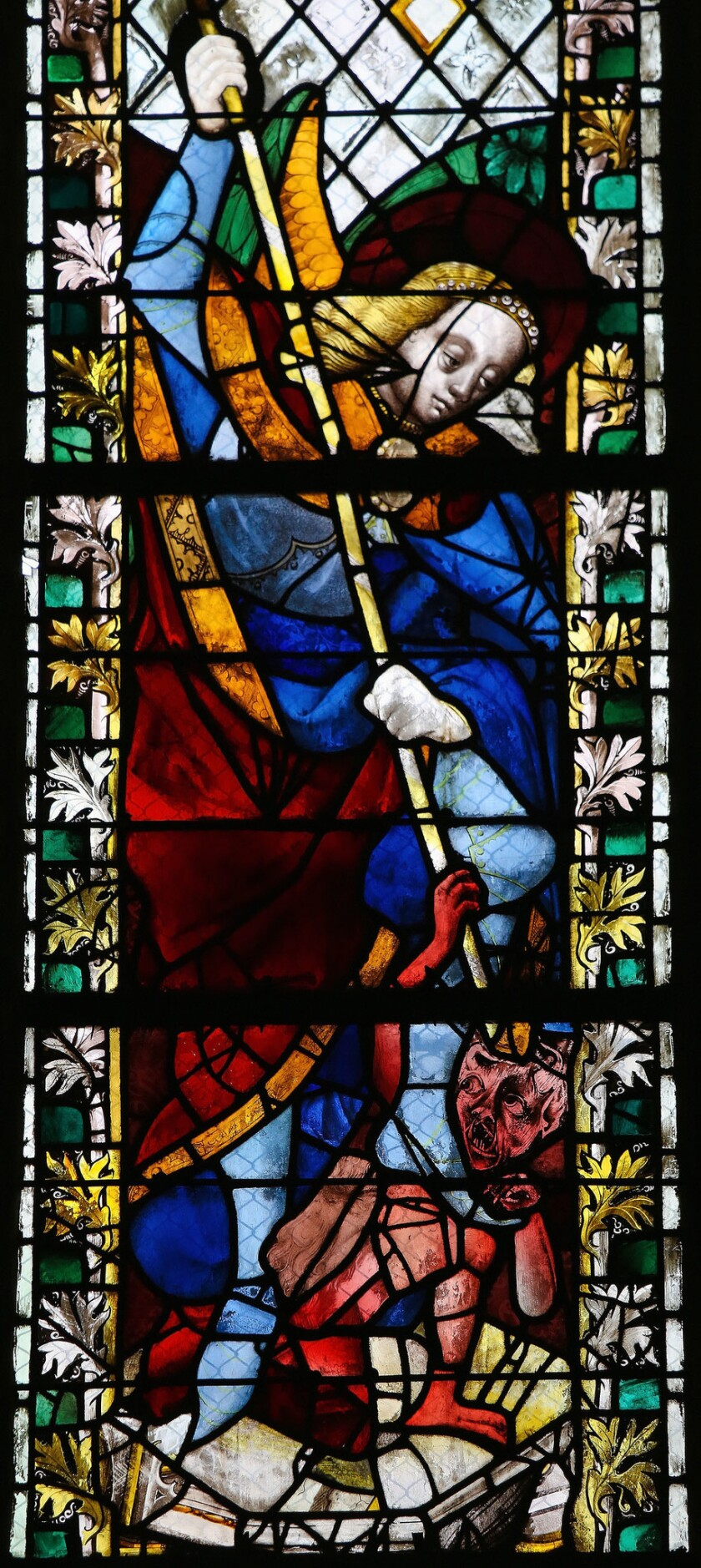 Saint Michael trampling Satan on a stained glass in the cathedral of Rouen, France.