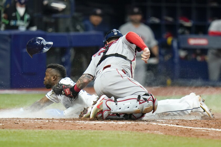 Tampa Bay Rays' Randy Arozarena steals home in the seventh inning past Boston Red Sox catcher Christian Vazquez in Game 1 of a baseball American League Division Series, Thursday, Oct. 7, 2021, in St. Petersburg, Fla. (AP Photo/Chris O'Meara)