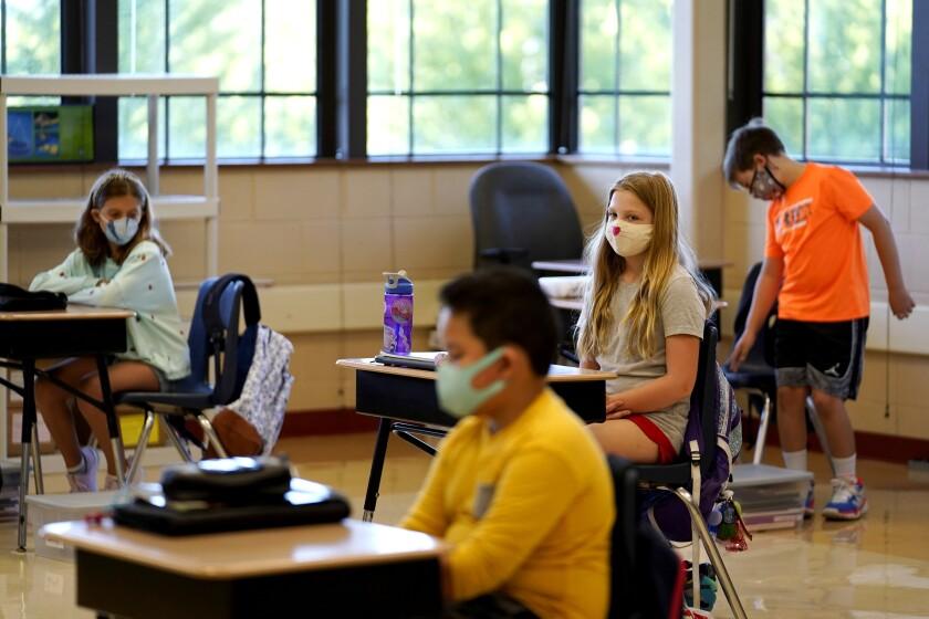 Estudiantes de quinto grado lucen máscaras en espera de su maestro en el aula.