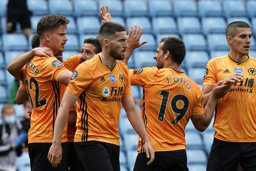 Wolverhampton's Leander Dendoncker, left, celebrates after scoring against Aston Villa in Birmingham, England on June 27.