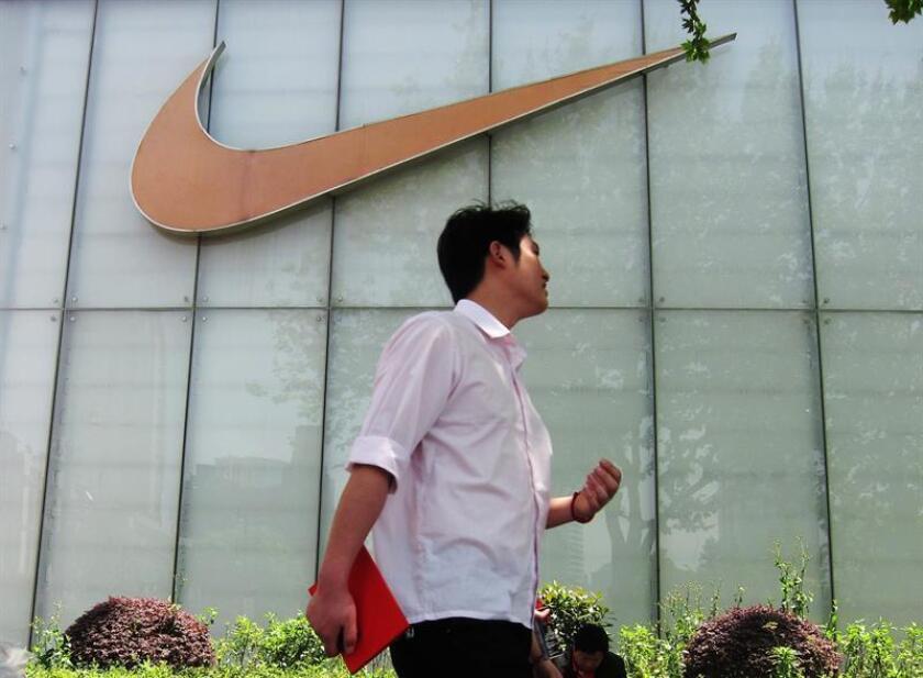 Un hombre pasa junto al letrero de una tienda Nike. EFE/Archivo