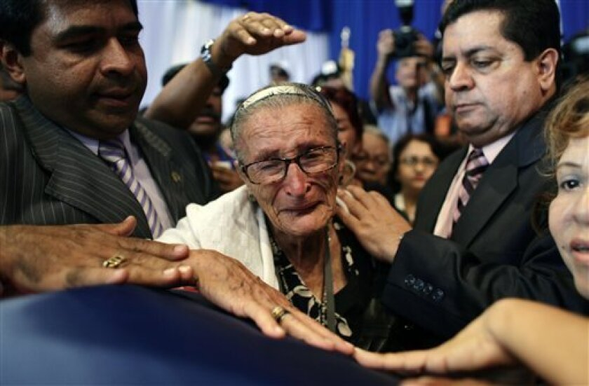 A supporter of Venezuela's late President Carlos Andres Perez reacts over the coffin containing his remains at the Action Democratic party headquarters in Caracas, Venezuela, Wednesday, Oct. 5, 2011. Perez's remains arrived to Venezuela Tuesday, nine months after his death in Miami set off a bitter family feud over his final resting place. (AP Photo/Ariana Cubillos)