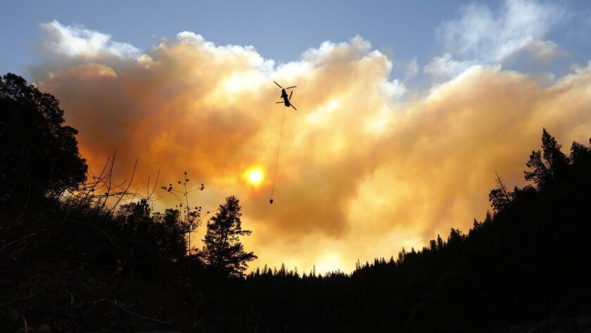 Helicopters drop water along the North Fork of the Feather River outside Pulga, Calif., where the Camp fire may have started.