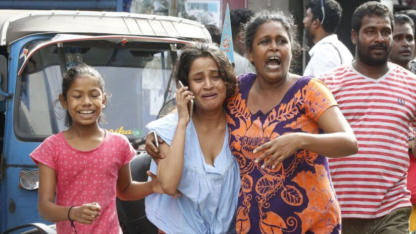People run for safety as authorities announce an evacuation Monday after a van containing explosives was found near a church in Colombo.