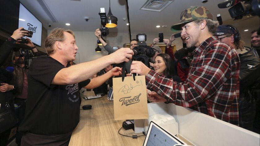 Canopy Growth CEO Bruce Linton, left to right, passes a bag with the first legal cannabis for recrea