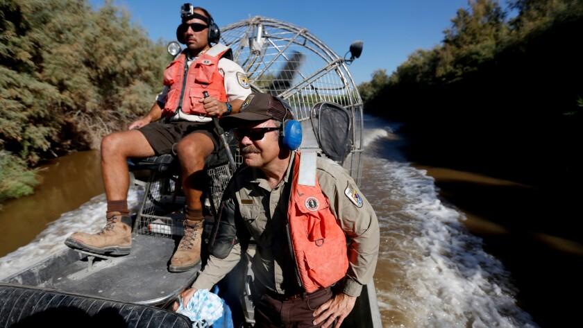 Chris Schoneman (right) and Aaron Eaton ride along the Alamo River.