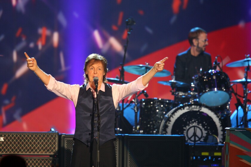 Paul McCartney, shown performing during a 50th anniversary Beatles television tribute, returns to tour after illness.