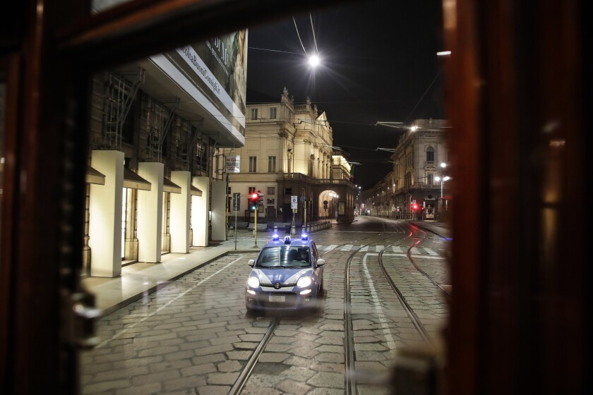 A police car follows a tram streetcar running along an empty street by the La Scala theater, in Milan, northern Italy, early Sunday, Oct. 25, 2020. Since the 11 p.m.-5 a.m. curfew took effect last Thursday, people can only move around during those hours for reasons of work, health or necessity. (AP Photo/Luca Bruno)