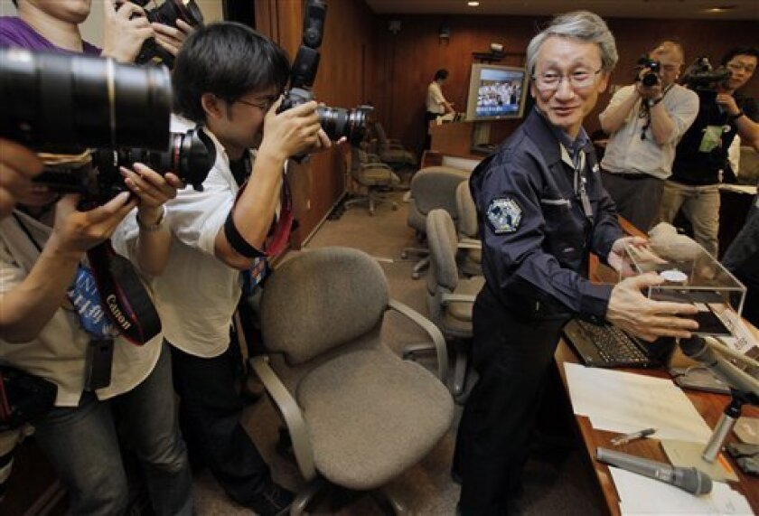 Hayabusa probe asteroid exploration project manager Junichiro Kawaguchi poses for photographers during a press conference at Japan Aerospace Exploration Agency (JAXA) in Sagamihara, near Tokyo, early Monday, June 14, 2010. Hayabusa's sampler capsule return to the earth after traveling 2.5 billion m