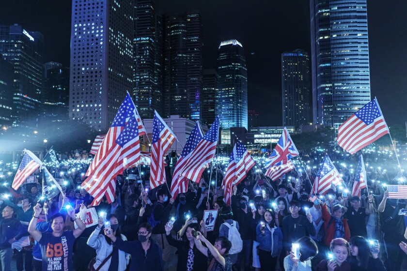 """HONG KONG, CHINA -- THURSDAY, NOVEMBER 28, 2019: Singing the """"star spangle banner,"""" waving American flags and waving banners bearing the protest slogan: """"Liberate Hong Kong, revolution of our times,"""" Pro-democracy demonstrators gather for a Thanksgiving rally to commemorate President Trump signing the Hong Kong Human Rights and Democracy Act into law, at the Central district of Hong Kong, on Nov. 28, 2019. The Hong Kong Human Rights and Democracy Act requires an annual review of whether Hong Kong retains enough autonomy to justify its special trade status with the U.S. The semi-autonomous Chinese territory has separate legal and economic systems as a result of its history as a British colony.(Marcus Yam / Los Angeles Times)"""