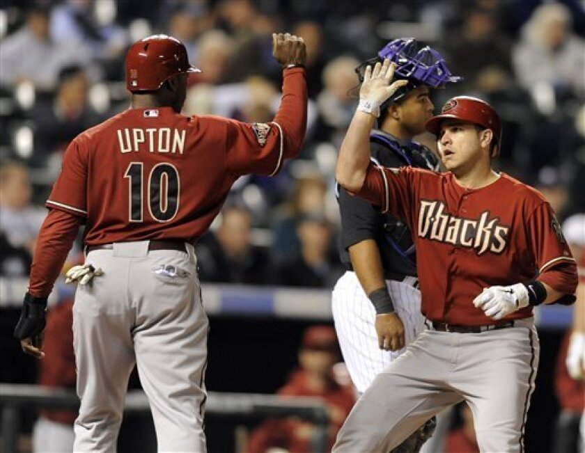 Arizona Diamondbacks' Miguel Montero , right, high-fives Justin Upton (10) after hitting a two-run home run off Colorado Rockies starting pitcher Kevin Millwood during the third inning of a baseball game on Wednesday, Sept. 7, 2011, in Denver. (AP Photo/Jack Dempsey)