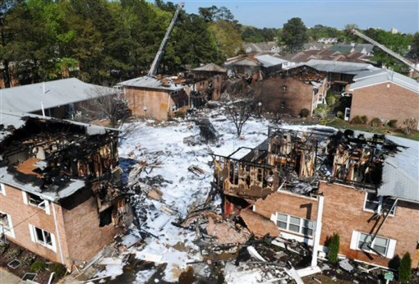 The scene of a jet crash is covered in foam on Friday, April 6, 2012, in Virginia Beach, Va. Two Navy pilots ejected from a fighter jet Friday, sending the unmanned plane careening into a Virginia Beach apartment complex and tearing the roof off at least one building that was engulfed in flames, officials said. Six people, including both pilots, were taken to hospitals, officials said. The Navy said both aviators on board the jet ejected before it crashed around noon and were being taken to hospitals for observation. (AP Photo/U.S. Navy, Petty Officer 3rd Class Antonio P. Turretto Ramos)