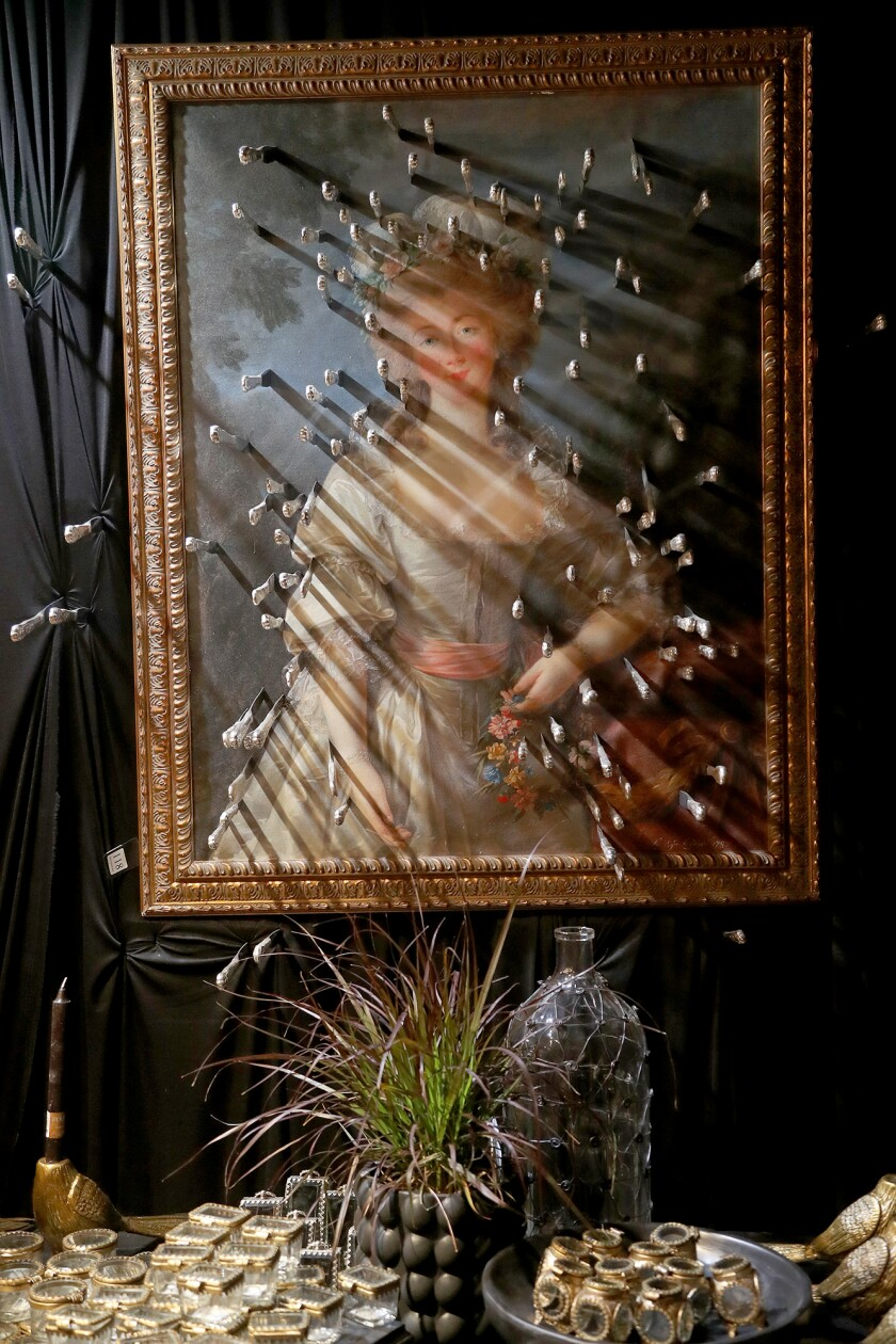 """A painting decorated with dozens of knives hangs at """"Cabinet of Curiosities"""" at Roger's Gardens in Corona del Mar."""