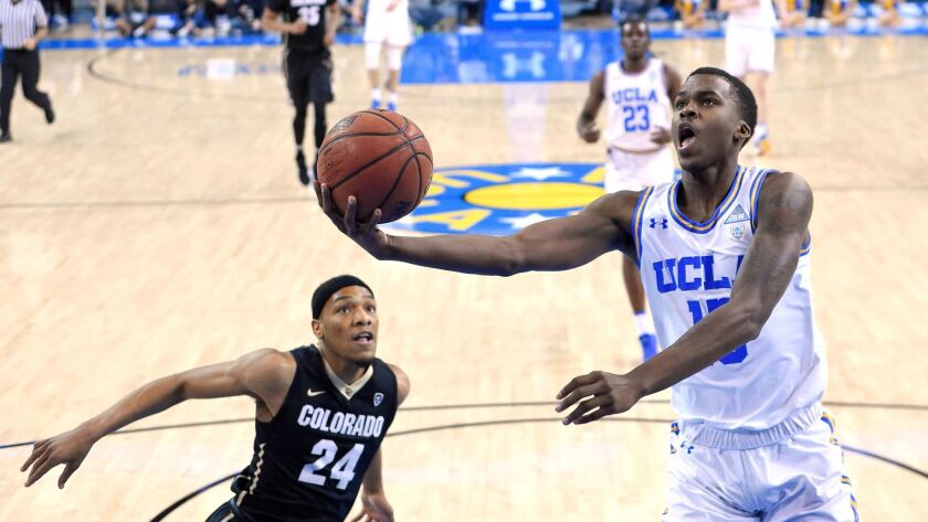 UCLA guard Kris Wilkes shoots as Colorado guard George King defends during the first half.