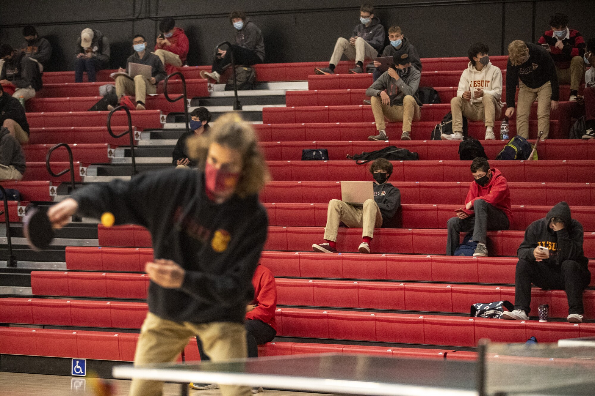 A student plays pingpong while others sit in the school gymnasium bleachers.
