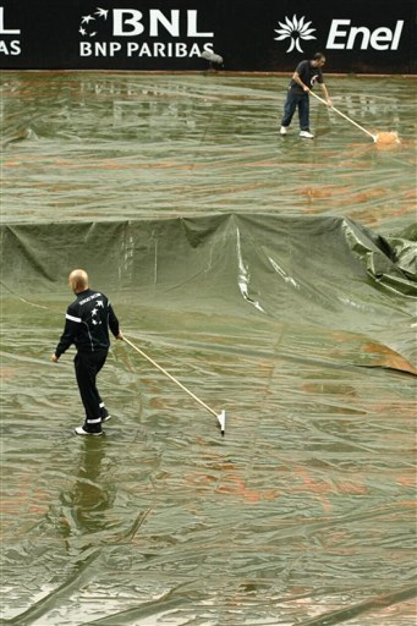 Maintenance workers remove water from a protective canvas during the final match between Spain's David Ferrer of Spain and Rafael Nadal, at the Rome Masters tennis tournament in Rome, Sunday, May 2, 2010. The match was suspended because of the rain. (AP Photo/Pier Paolo Cito)