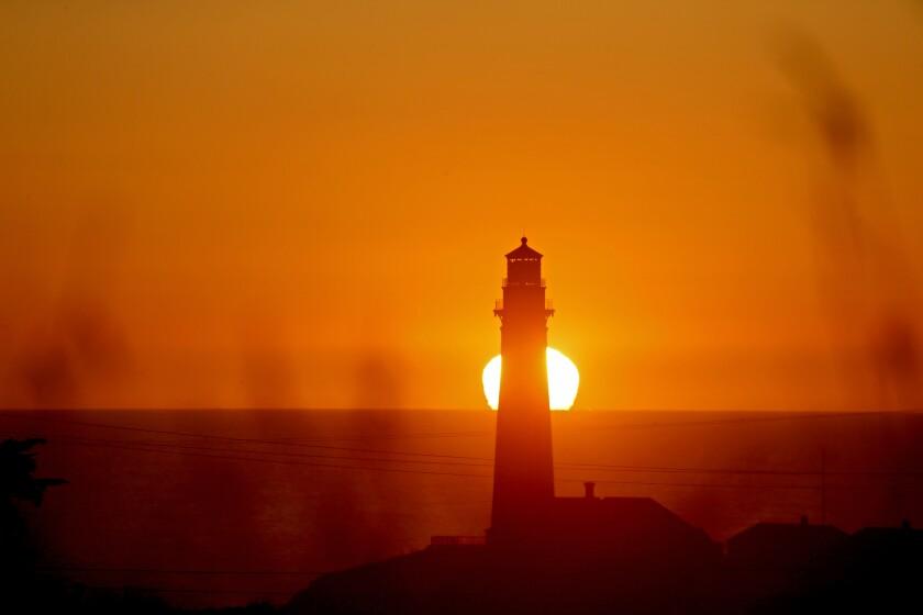 Sunset behind a lighthouse.