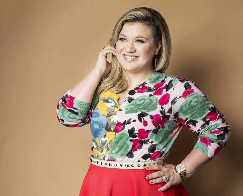 "FILE - In this March 4, 2015 file photo, American singer and songwriter Kelly Clarkson poses for a portrait to promote her album ""Piece by Piece"" in New York. Clarkson has written a new song and a bedtime story for kids. ""River Rose and the Magical Lullaby,"" will be released in October by HarperCol"