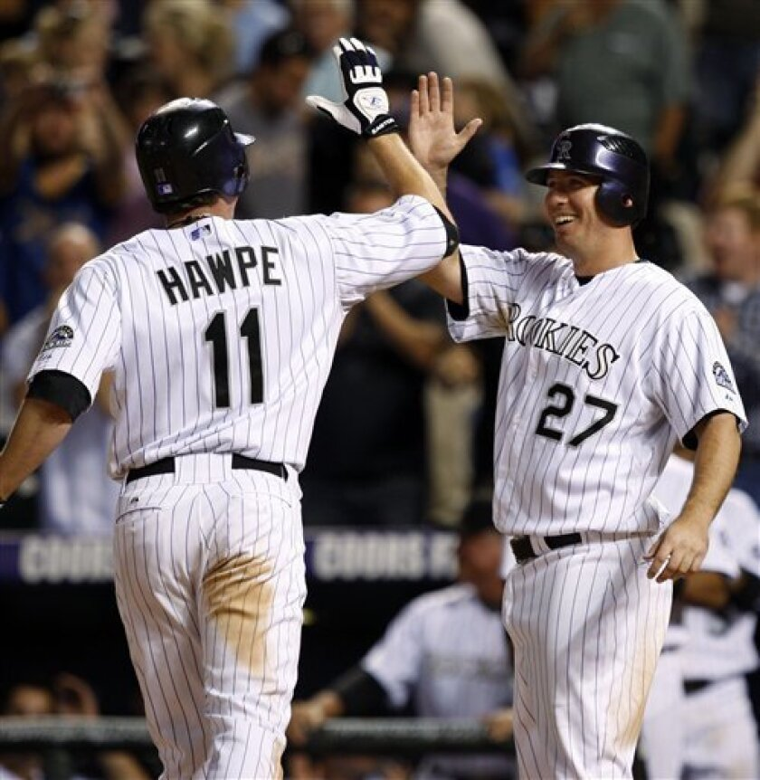 Colorado Rockies' Brad Hawpe, left, is congratulated by teammate Garrett Atkins as Hawpe crosses home plate after hitting a two-run home run off Milwaukee Brewers relief pitcher Brian Shouse in the eighth inning of the Rockies' 6-4 victory in a Major League baseball game on Friday, June 6, 2008, in Denver. (AP Photo/David Zalubowski)