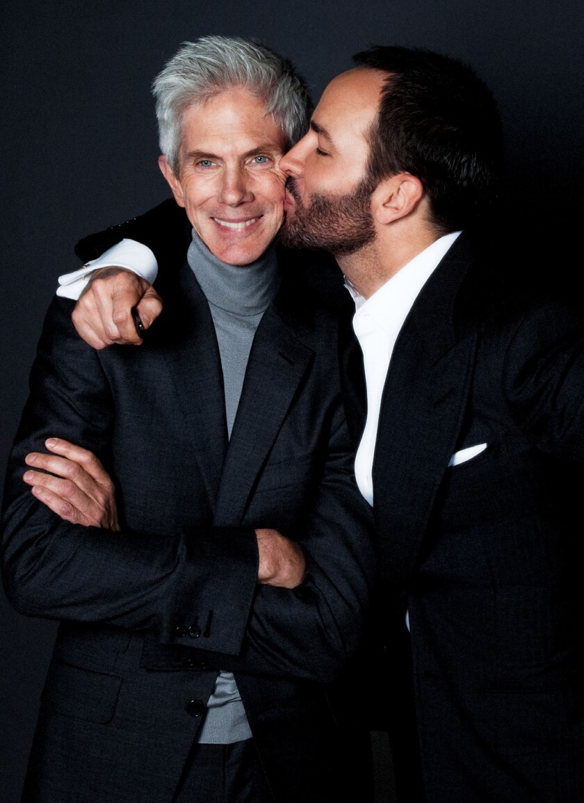 A man in a suit gets a kiss on the cheek.
