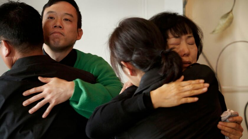 Hoona Jo, second from left, brother of Ara Jo, and their mother Yoo Sook Jo are consoled by mourners at Ara Jo's funeral in Koreatown.