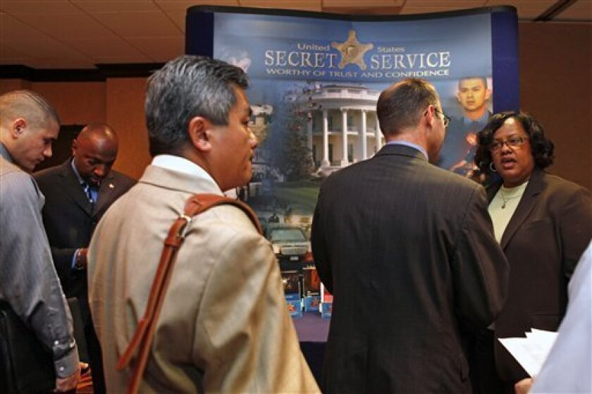 Sgt. Dee Moore, right, with the Secret Service, answers questions from a line of job seekers at a career fair in McLean, Va. on Friday, May 8, 2009. The pace of layoffs slowed in April when employers cut 539,000 jobs, the fewest in six months. But the unemployment rate climbed to 8.9 percent, the highest since late 1983, as many businesses remain wary of hiring given all the economic uncertainties. (AP Photo/Jacquelyn Martin)