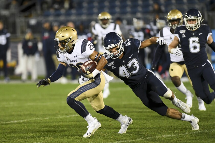 Navy wide receiver Garrett Winn (26) is chased down by Connecticut linebacker Jackson Mitchell during the Midshipmen's 56-10 victory on Friday.