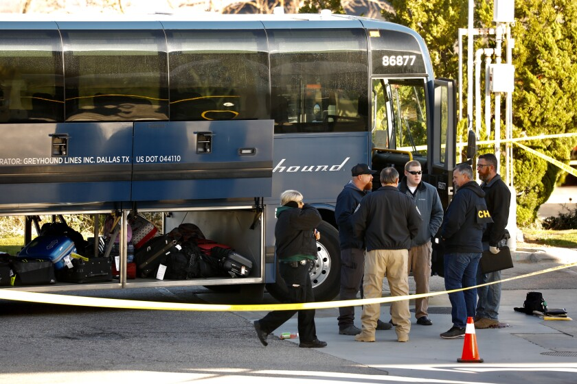 Investigators gather in Lebec, Calif., outside a Greyhound that was the scene of a fatal shooting.