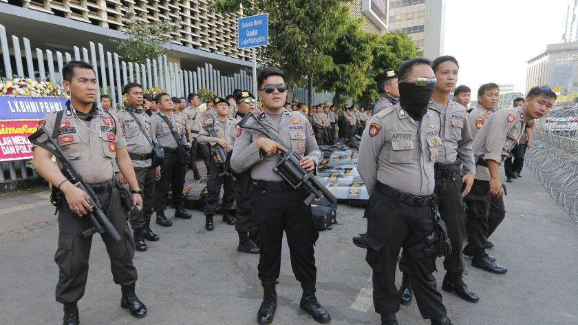 Riot police stand guard outside the General Election Supervisory Board building in anticipation of p