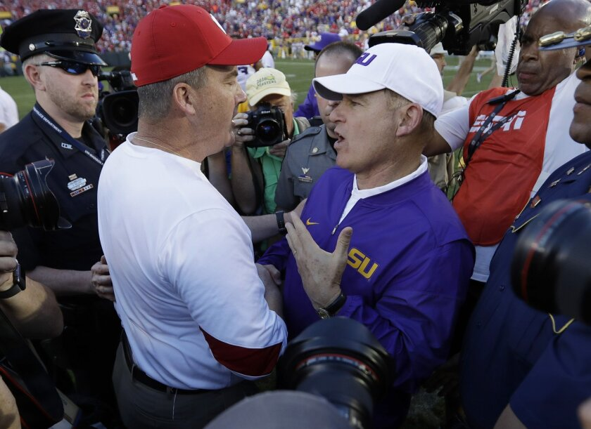 FILE - In this Saturday, Sept. 3, 2016, file photo, LSU head coach Les Miles talks to Wisconsin head coach Paul Chryst after Wisconsin won 16-14 in an NCAA college football game in Green Bay, Wis. In recent years, voters have become more comfortable making dramatic shifts in early season polls ,  w