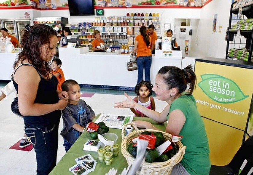 Yelena Zelster, with the Urban and Environmental Policy Institute, right, talks with Guadalupe Garcia and her kids Ricardo, 5, and Guadalupe, 2, as they give out a bag of avocados at Prime Time Nutrition as part of the farm to WIC program.