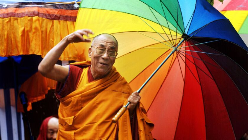 Tibetan spiritual leader the Dalai Lama greets people in Huy, Belgium on May 29, 2006.