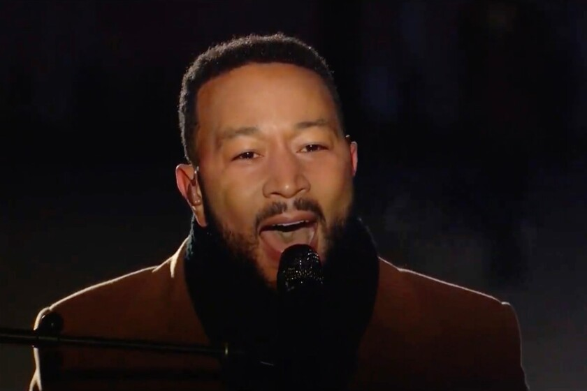 John Legend singing into a microphone
