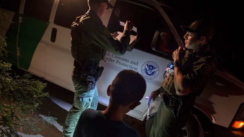 Border Patrol agents process an unaccompanied minor for transportation after the boy illegally crossed the Rio Grande on a raft in Hidalgo, Texas.