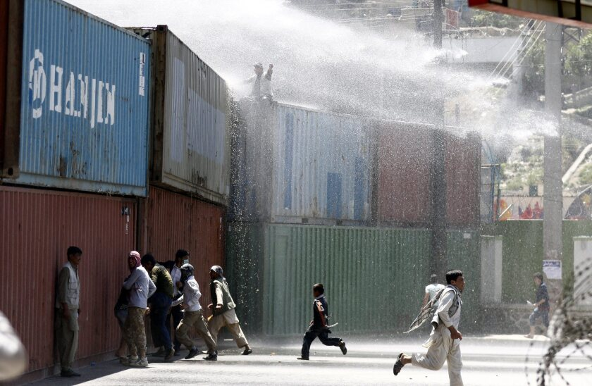 Police fire water cannons as protesters from the Hazara minority protest the rerouting of a power line.