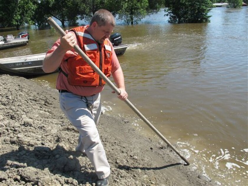 In a June 28, 2011 photo, Mark Vollmer, who becomes school superintendent Friday in Minot, N.D., uses a pole to inspect an earthen dike protecting Perkett Elementary School from floodwaters. Perkett is dry thus far but three other schools have been damaged, meaning more than 1,000 students will hav